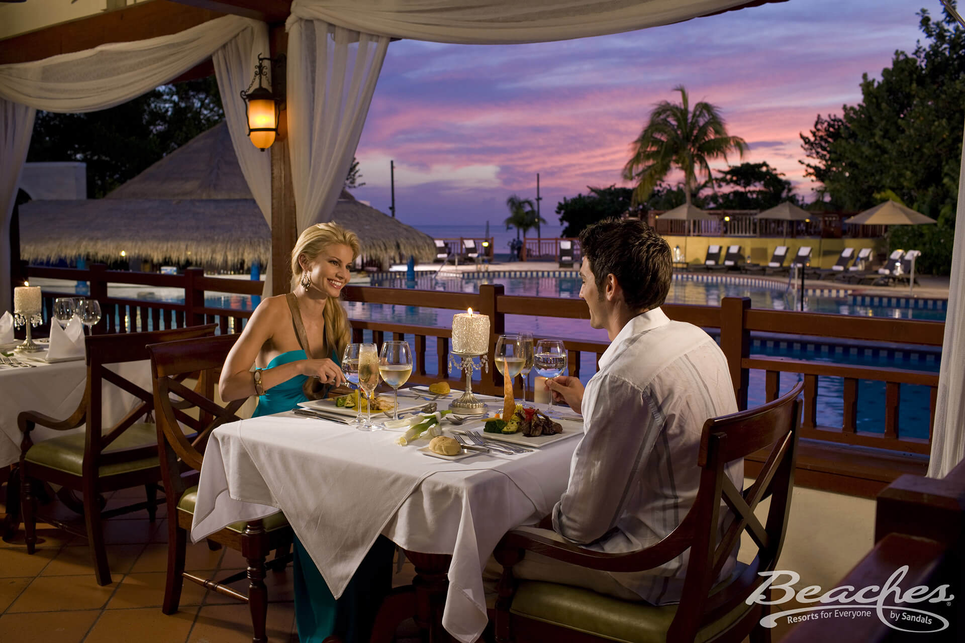 Couple dining at a restaurant at a Beaches All-Inclusive Resort by the pool in the evening