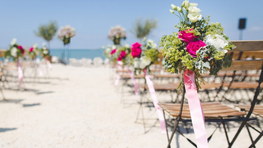 Pink and white flower bouquets placed on the side of chairs on the beach