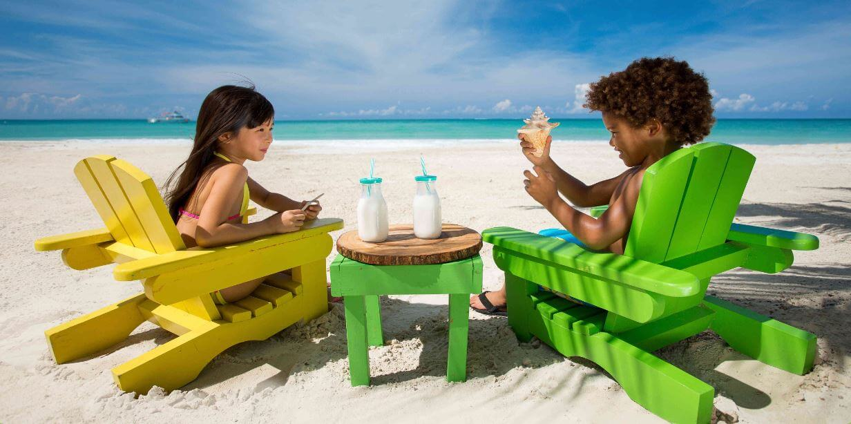 Two children sitting on the beach on vacation to the Caribbean. Both are sitting in painted wooden chairs with two bottles of milk on the table between them. Boy is holding a small conch shell